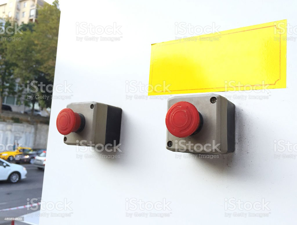 two red buttons on white wall with blank warning sign stock photo