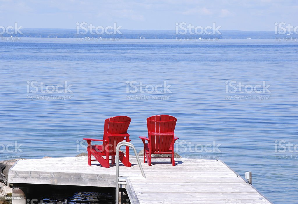 Two red chairs on a dock stock photo