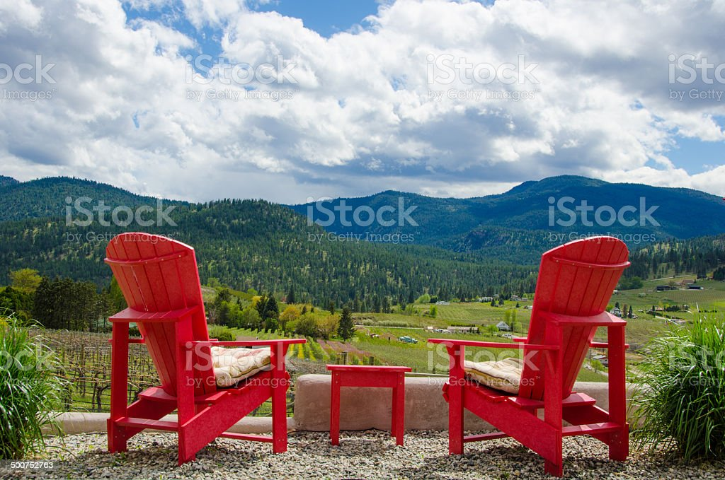 Two red chairs overlooking a vineyard stock photo