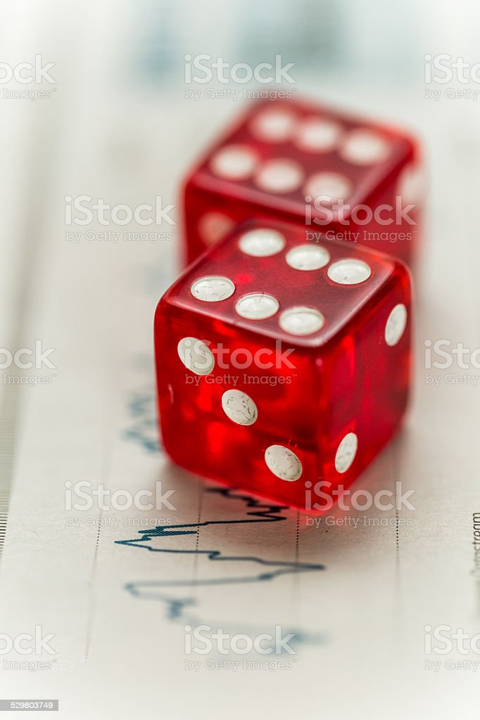 Two red dice and a graph displaying financial data stock photo