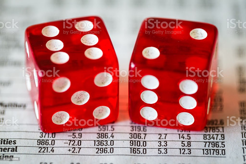 Two red dice on top of financial stock market data stock photo