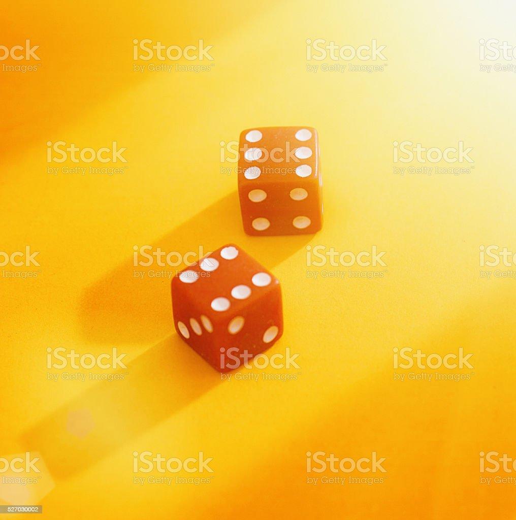 Two red dice score 12 on orange background stock photo