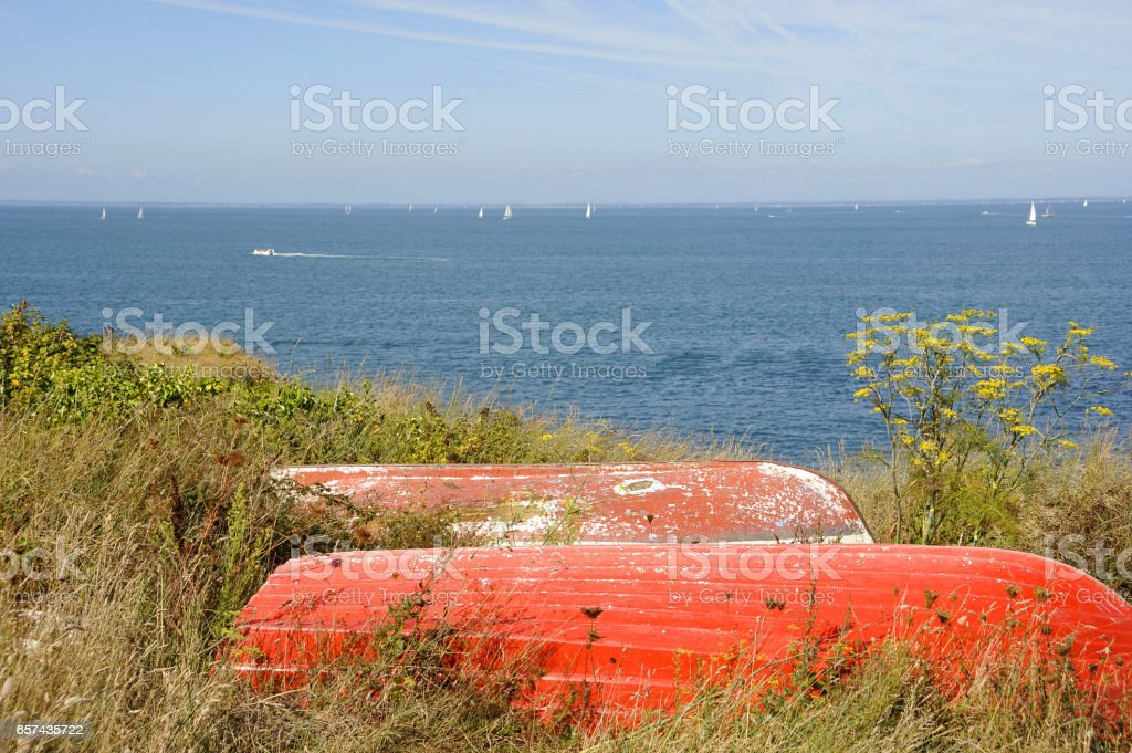 Two red dinghies on a cliff-top in the grass with blue sky and sea with yachts. stock photo