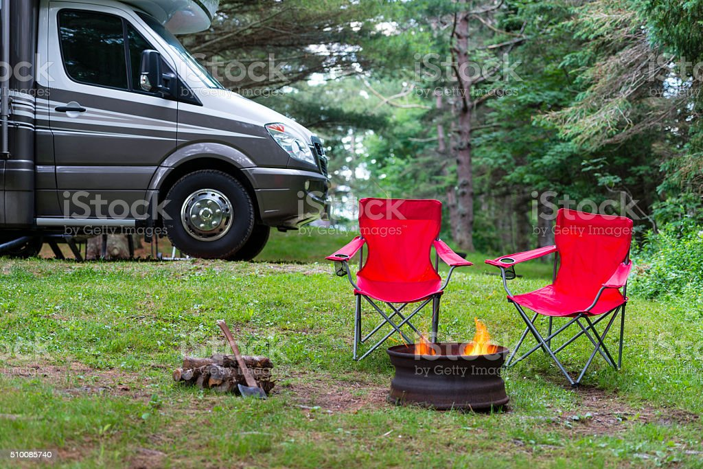 Two red folding chairs near campfire stock photo