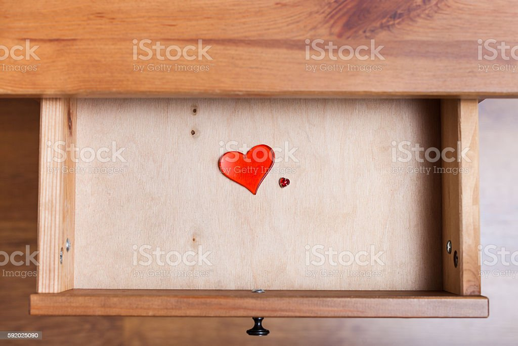 two red glass hearts in open drawer stock photo
