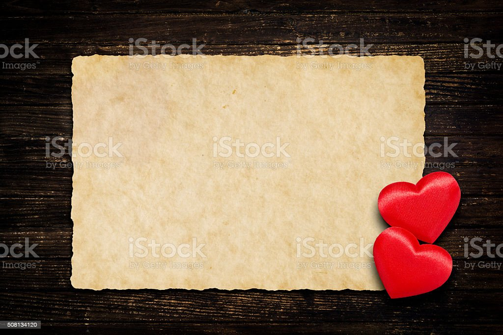 Two red hearts and vintage paper on weathered wooden background stock photo