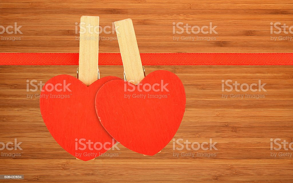 Two red hearts at ribbon over bamboo wood royalty-free stock photo