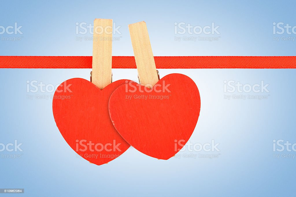 Two red hearts at ribbon over blue noise royalty-free stock photo