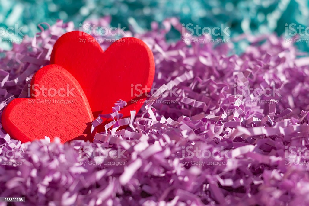 Two red hearts in purple and turquoise paper tinsel stock photo