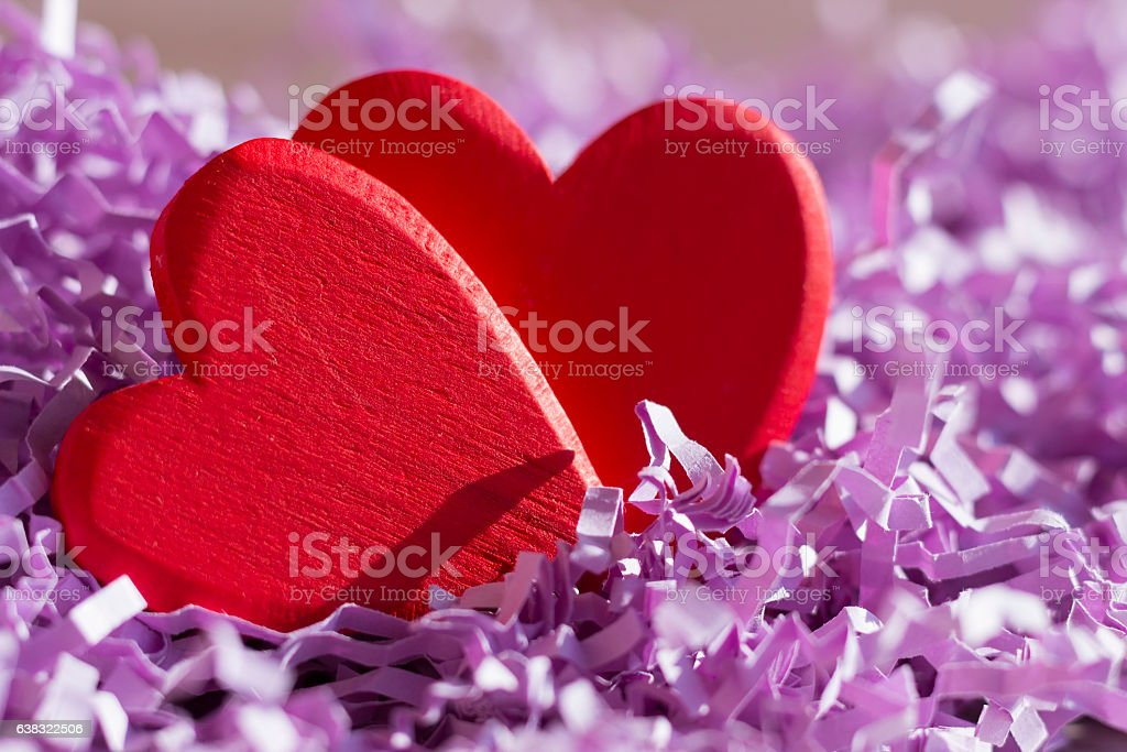 Two red hearts in purple paper tinsel stock photo