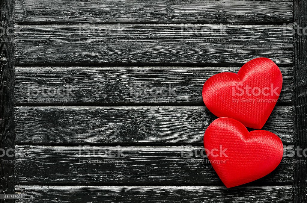 Two red hearts on black table stock photo