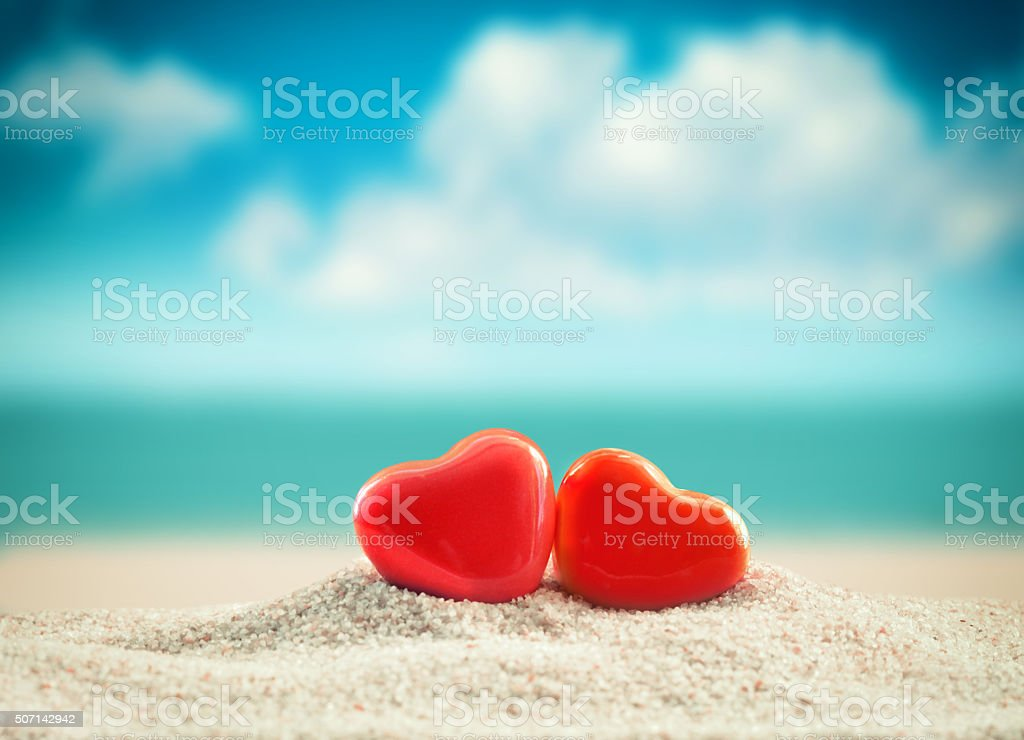 Two red hearts on the summer beach. Valentines day. stock photo
