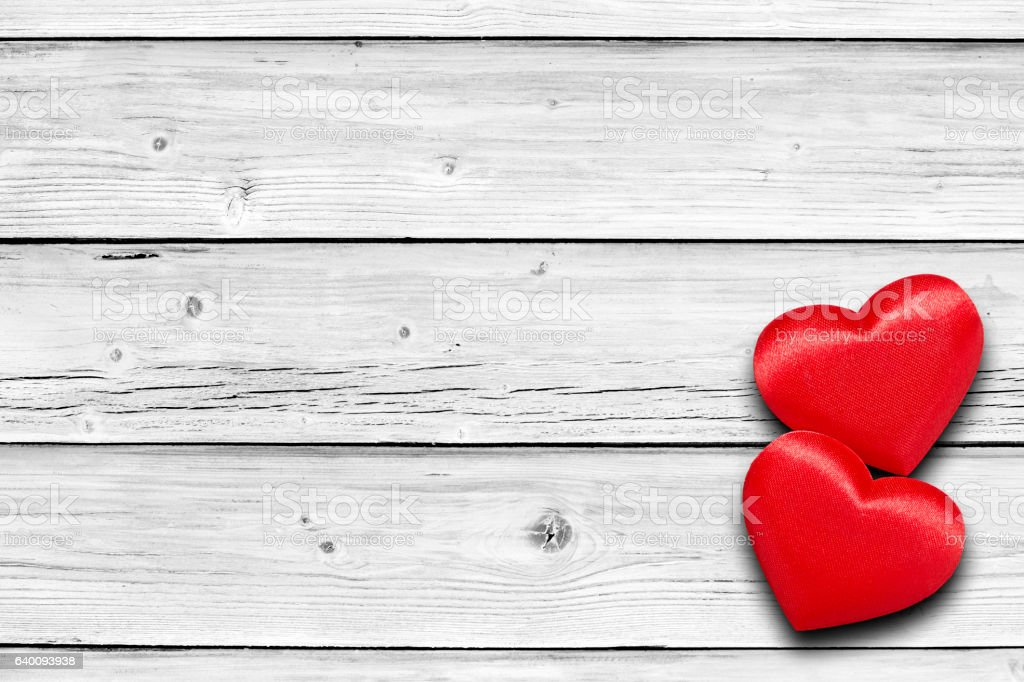 Two red hearts on white weathered wooden table stock photo