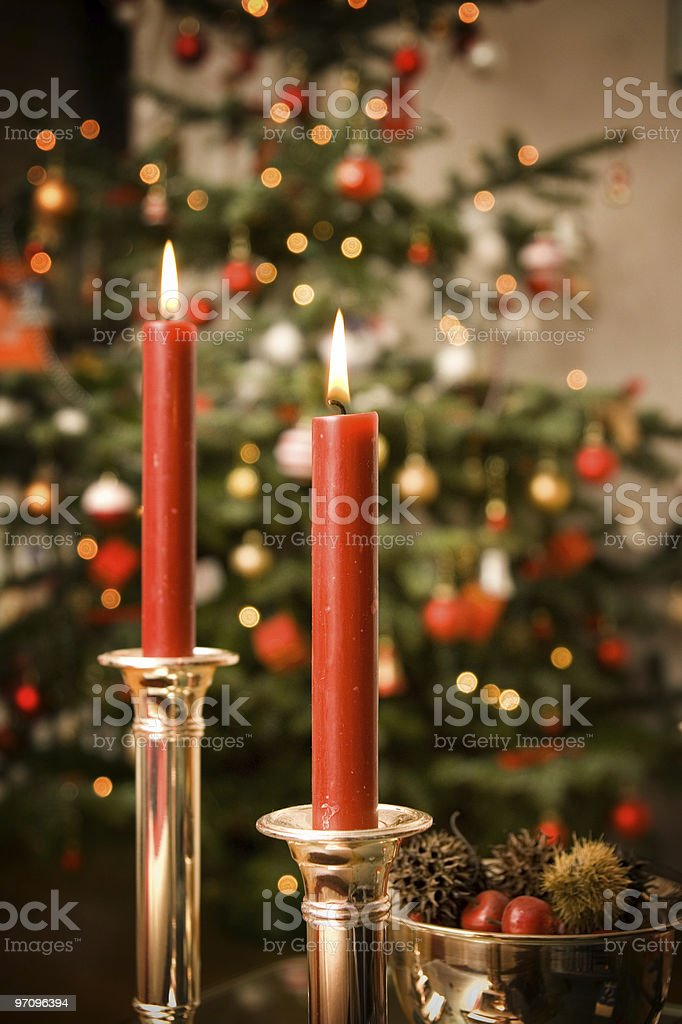 Two red lit candles with a Christmas tree in the background royalty-free stock photo