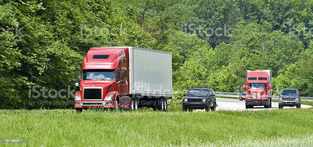 Two Red Semis In Interstate Traffic royalty-free stock photo