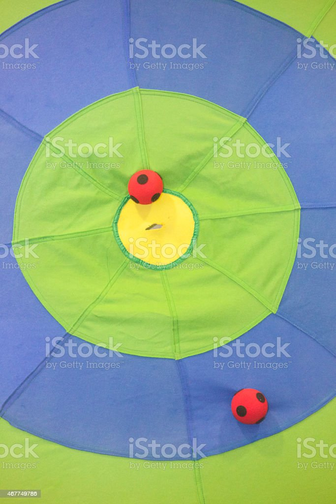 Two red sticky balls attached to a large toy target stock photo
