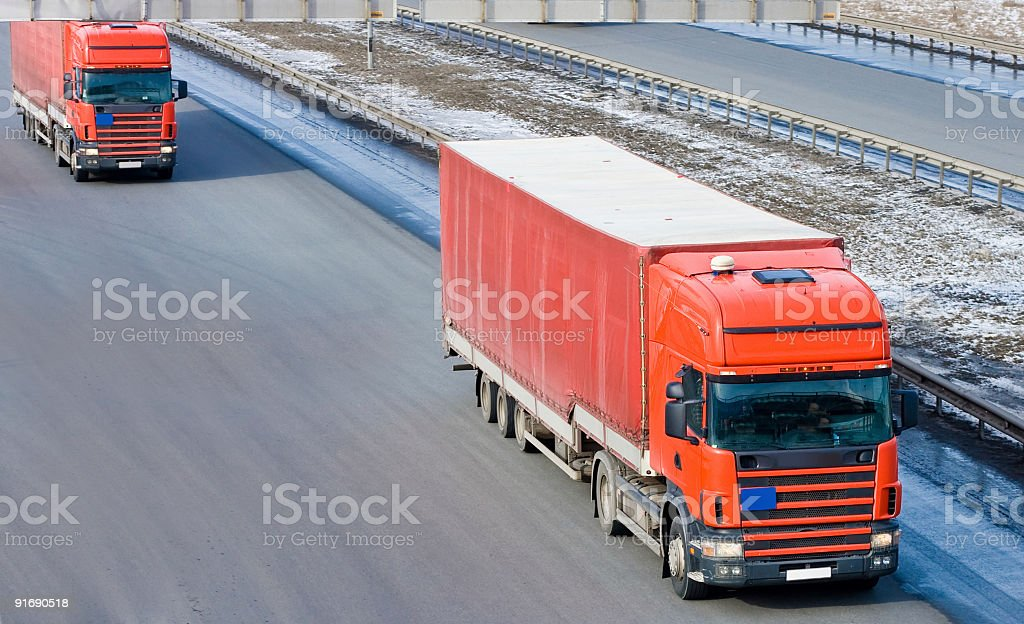 Two red tractor trailer trucks royalty-free stock photo