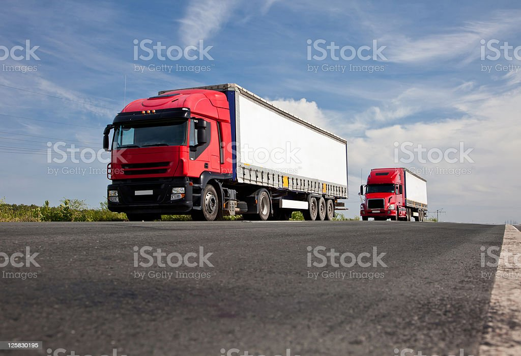 Two red trucks on road royalty-free stock photo
