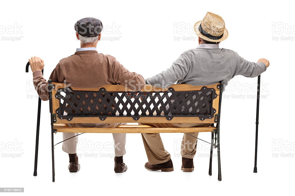 Two relaxed seniors sitting on a bench stock photo