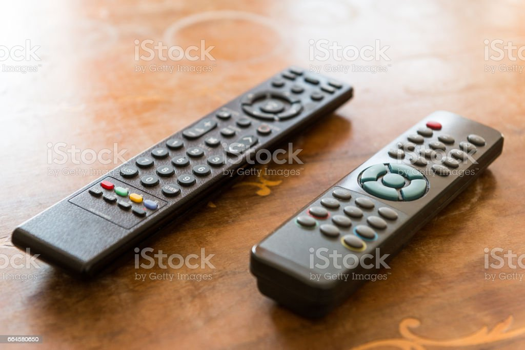two remote controller on a wodden table stock photo