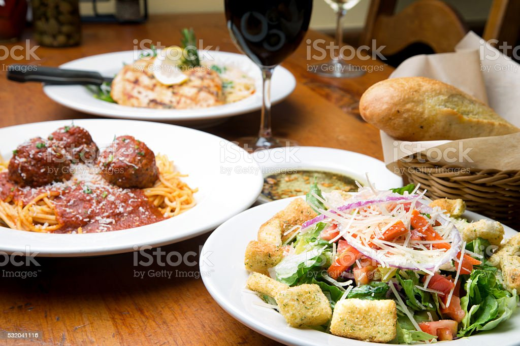 Two Restaurant Style Entrees With Salad And Bread stock photo