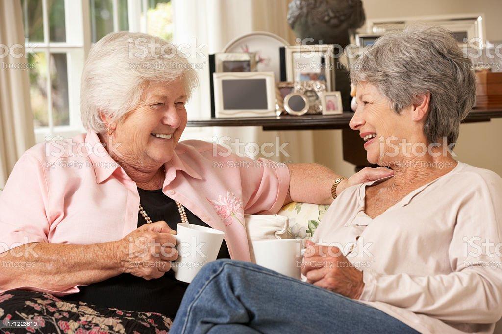 Two Retired Senior Female Friends Sitting On Sofa stock photo
