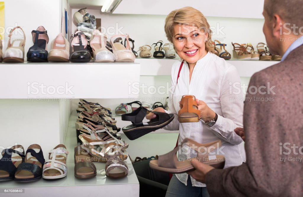 Two retirees together choosing pair of shoes in fashion store stock photo