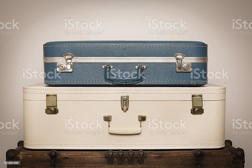 Two Retro Suitcases Stacked on Wood Trunk royalty-free stock photo