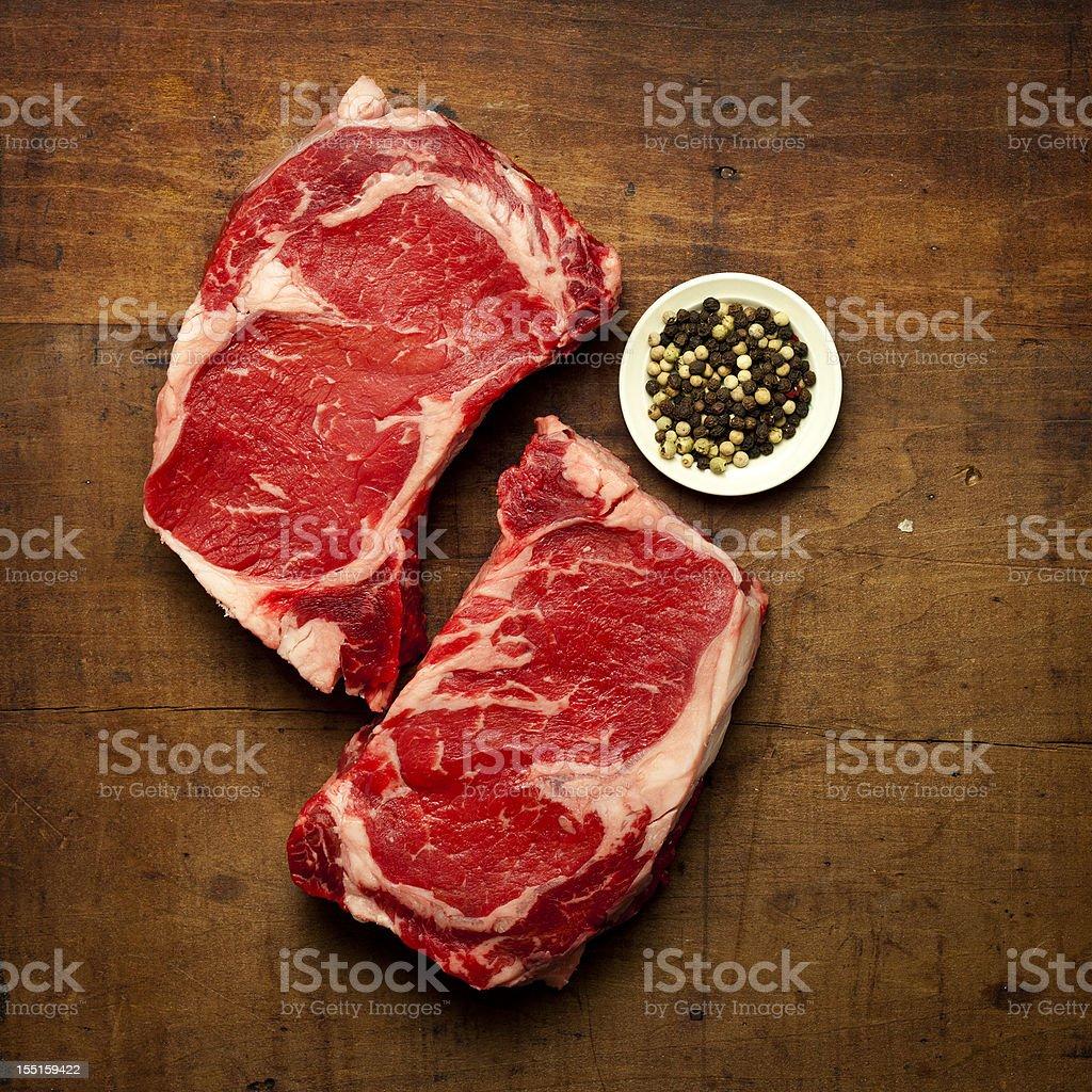 two rib-eye steaks and pepper stock photo