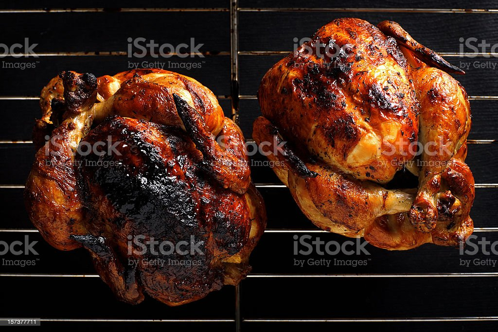 Two roasted chickens still on the grill stock photo