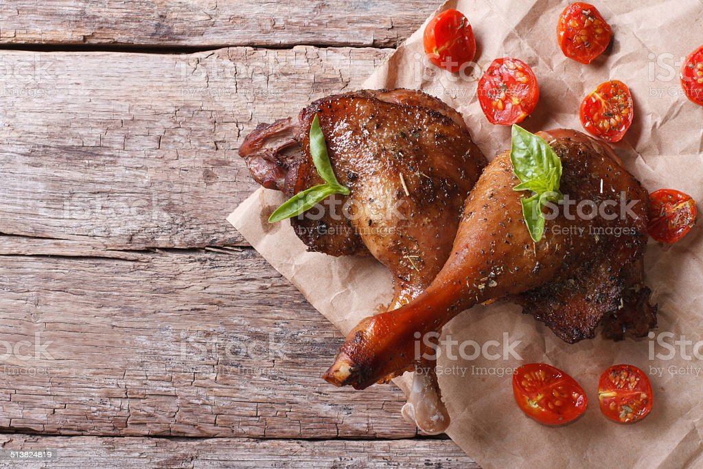 two roasted duck legs with basil and tomatoes stock photo