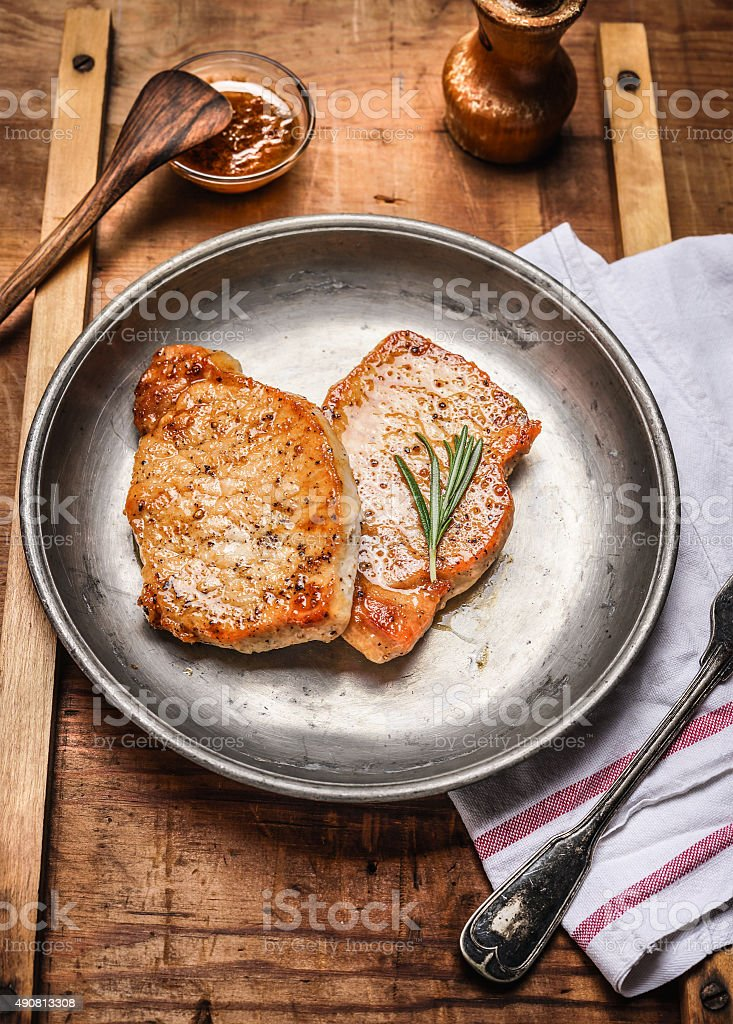 Two roasted pork steaks on rustic metal plate, close up stock photo