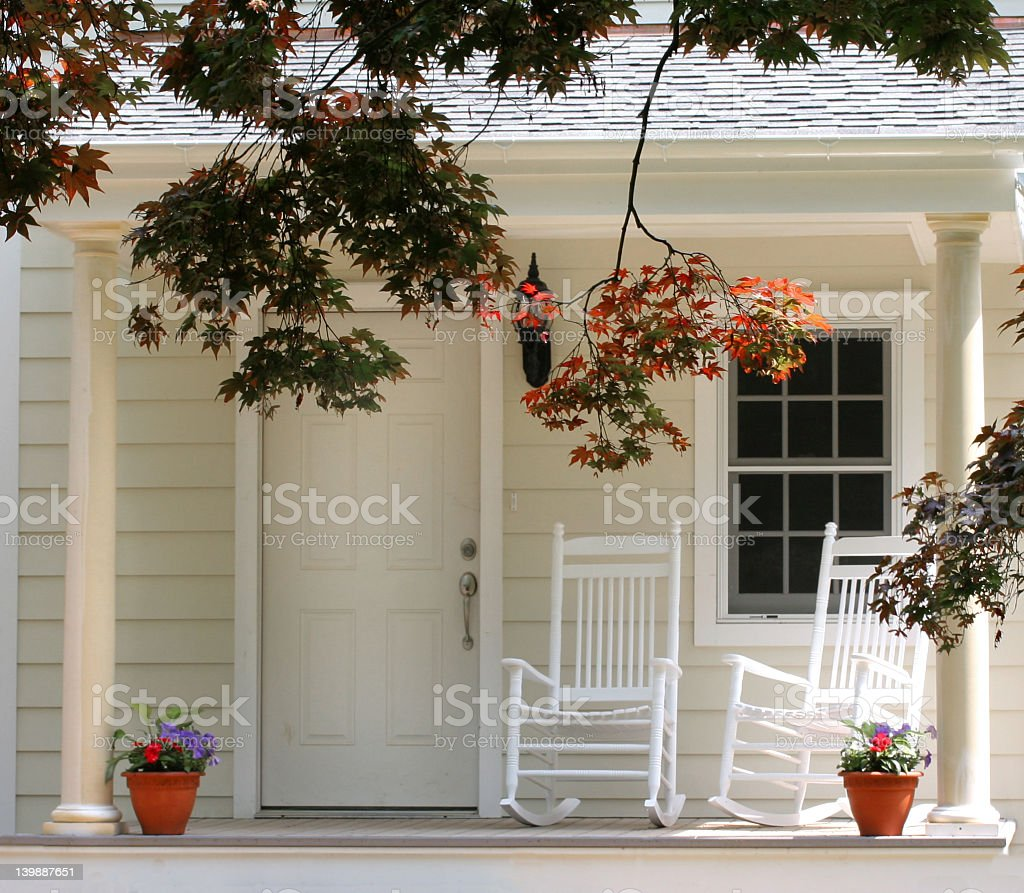 Two rocking chairs on a front porch in autumn stock photo