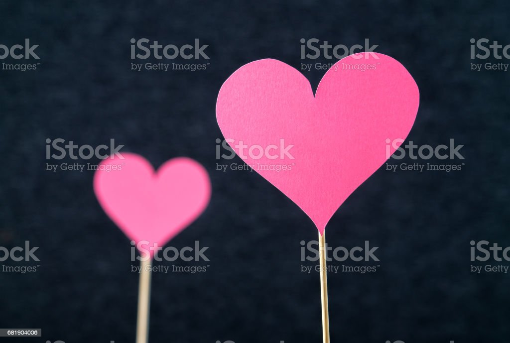 Two romantic hearts cut from cardboard or paper on wooden stick and dark background. Beautiful, handmade pink red love shapes. Simple anniversary, mother's, valentine's or women's day greeting card. stock photo