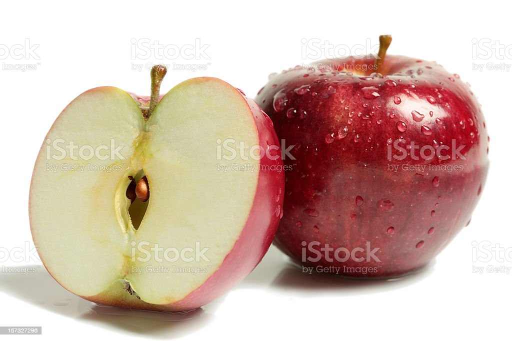 Two rosy red apples with one halved on white surface royalty-free stock photo