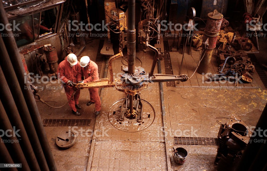 two roughnecks working on oil rig platform drill floor stock photo
