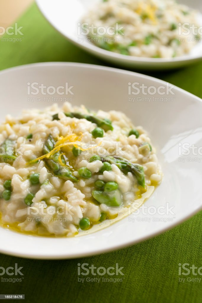 Two round plates served with spring risotto stock photo