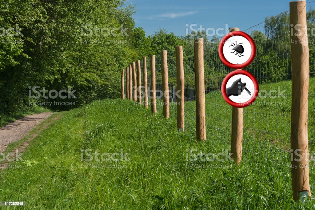 Two round red warning signs on a fence post in front of a green meadow. stock photo