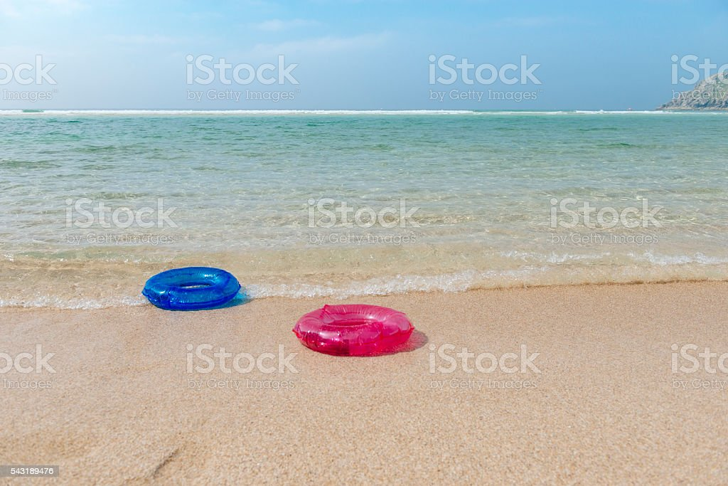 Two rubber rings on a beach, Pedn Vounder Cornwall stock photo