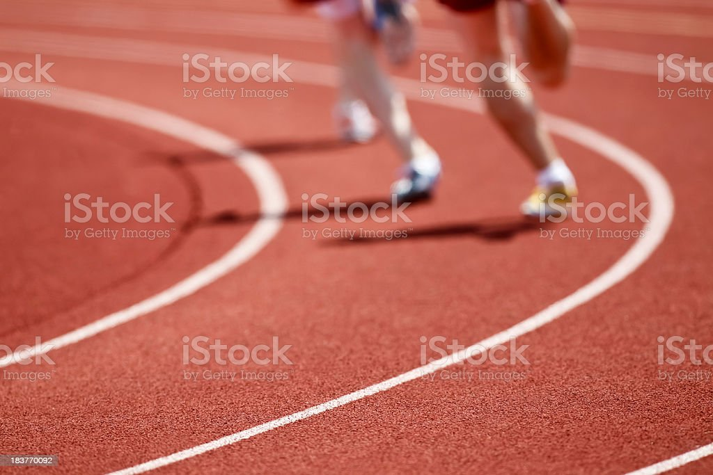 Two runners on a track in running shoes racing stock photo