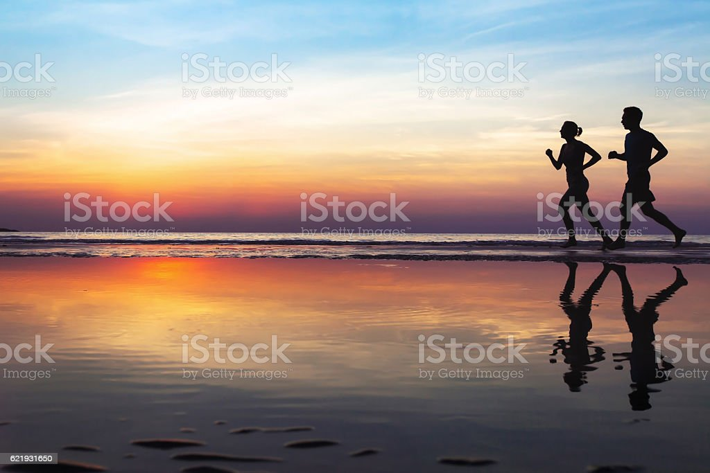 two runners on the beach, silhouette stock photo