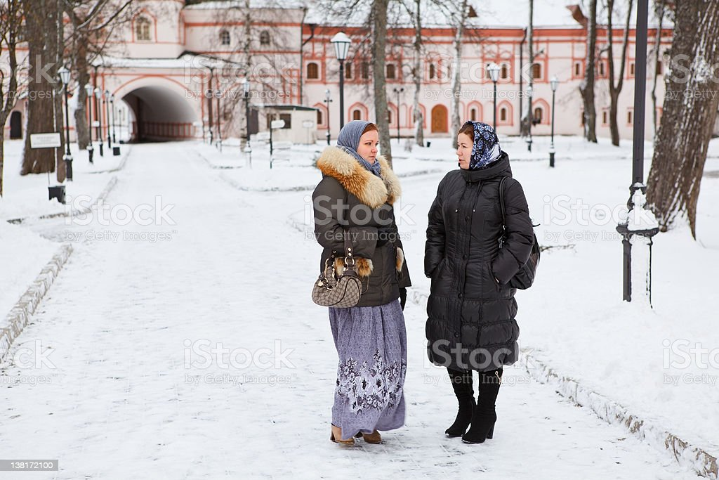 Two Russian women in winter clothes and headscarfes talking royalty-free stock photo