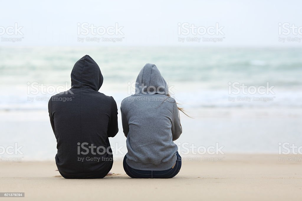 Back view of two sad teenagers sitting on the sand of the beach and...