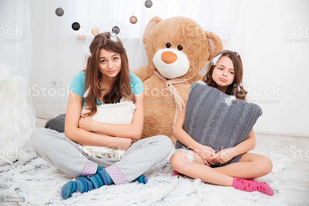 Two sad tired sisters sitting and hugging pillows stock photo