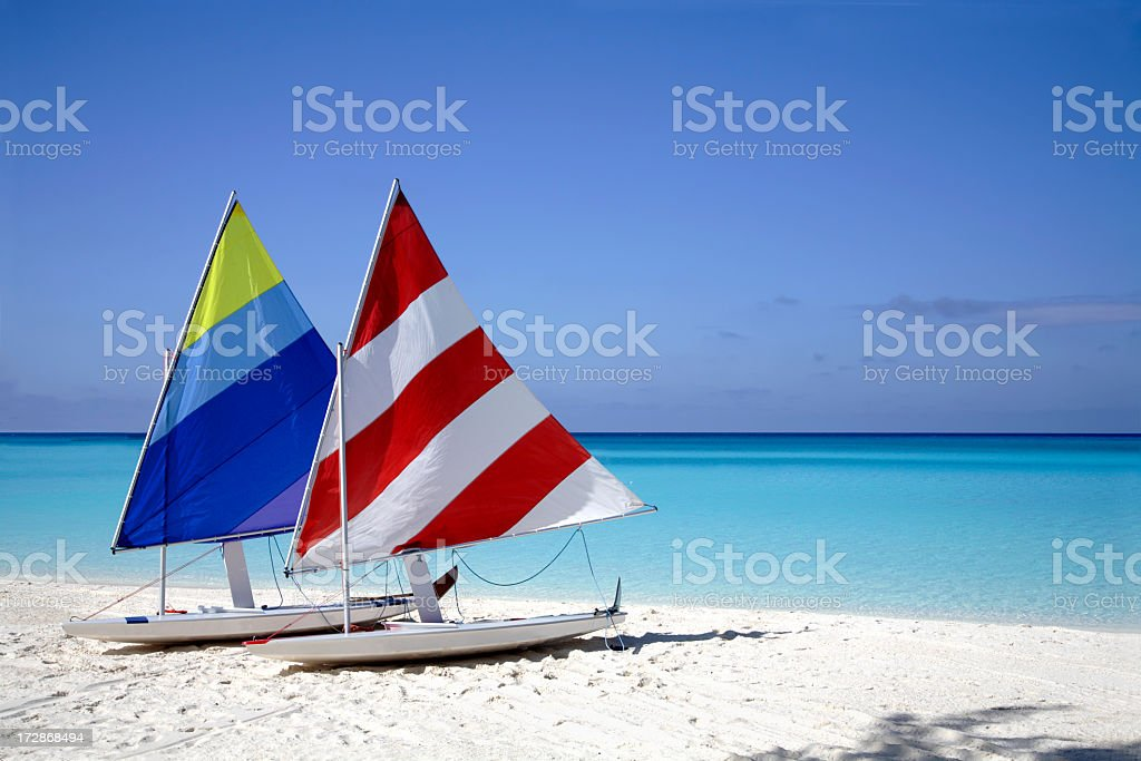 Two sailboats on the beach near the shore stock photo