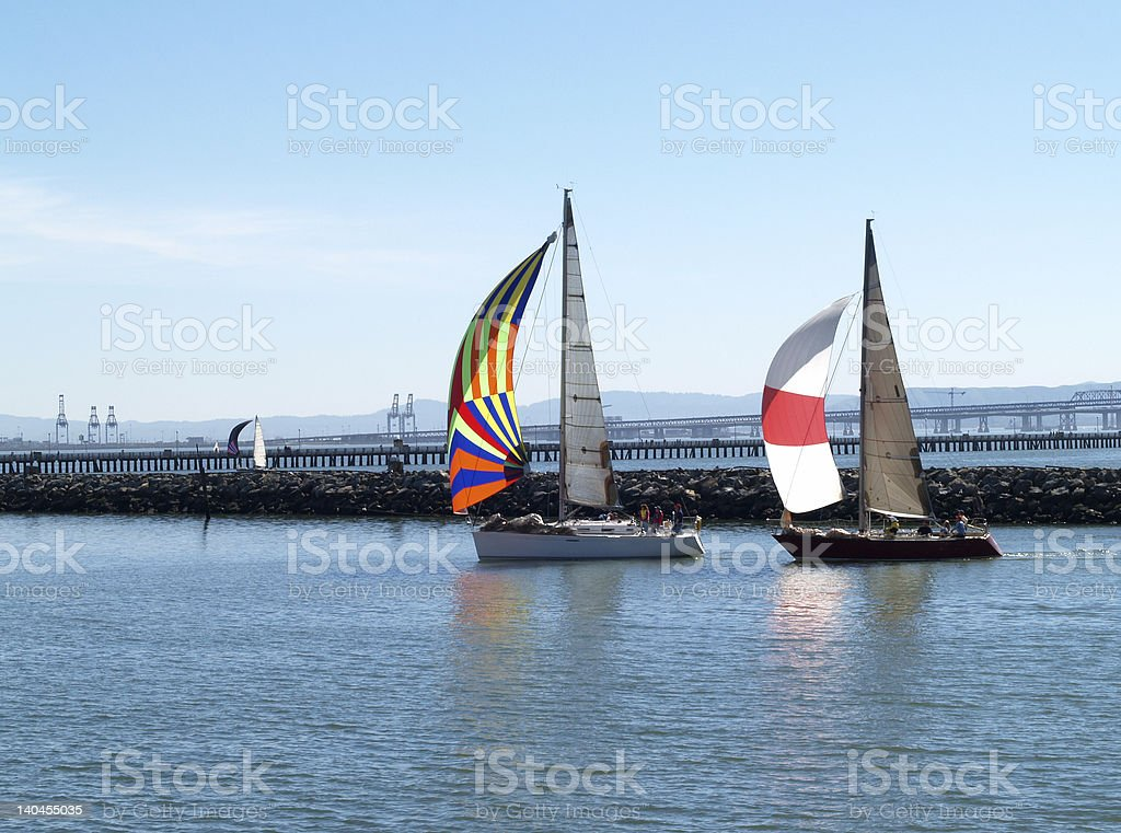 Two Sailboats under Spinnakers running into port stock photo