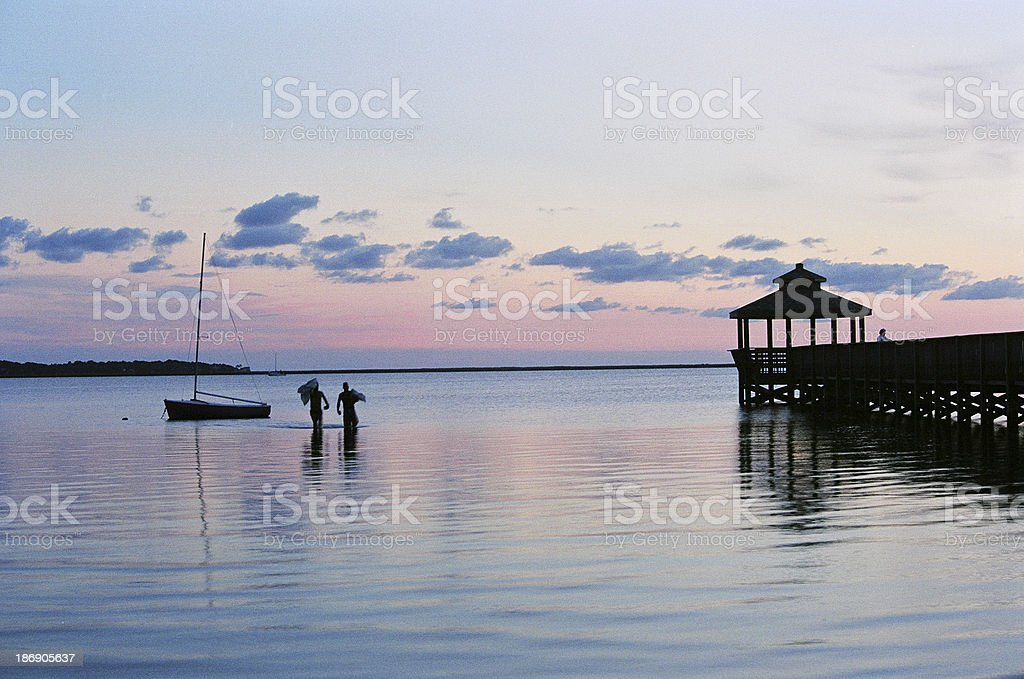 Two sailors hauling in the sails with reddish sunset sky stock photo