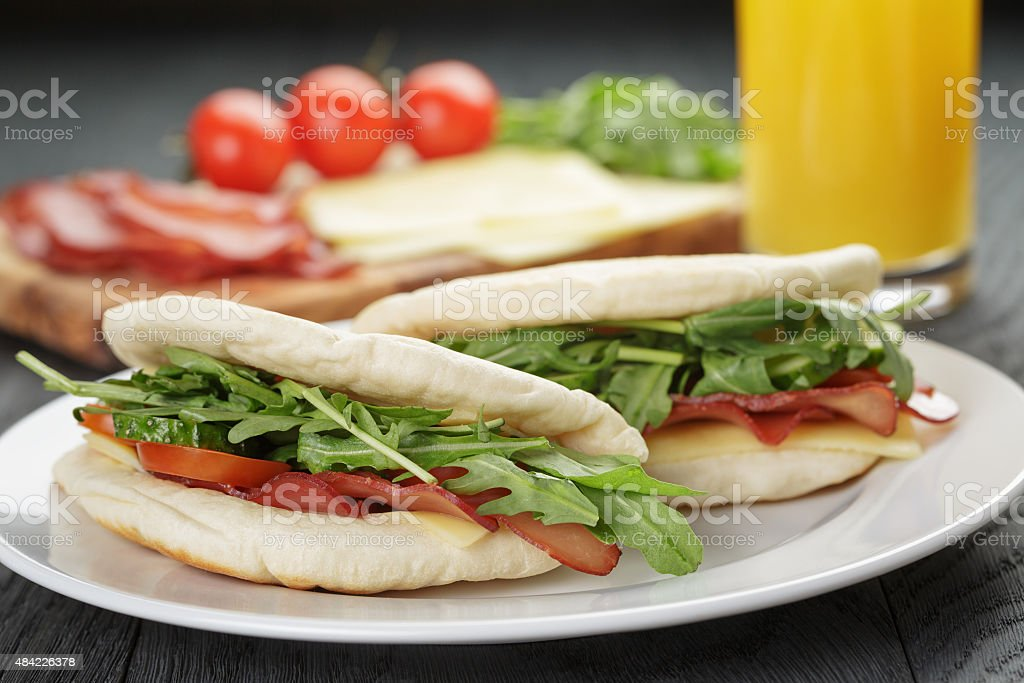 two sandwiches with ham arugula and tomatoes in pita bread stock photo