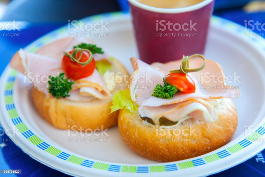 Two sandwiches with ham, parsley and cherry lying on a plate in a cafe stock photo