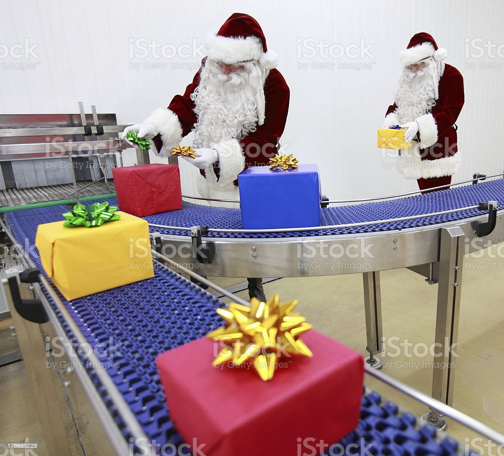 Two santa clauses working at production line royalty-free stock photo